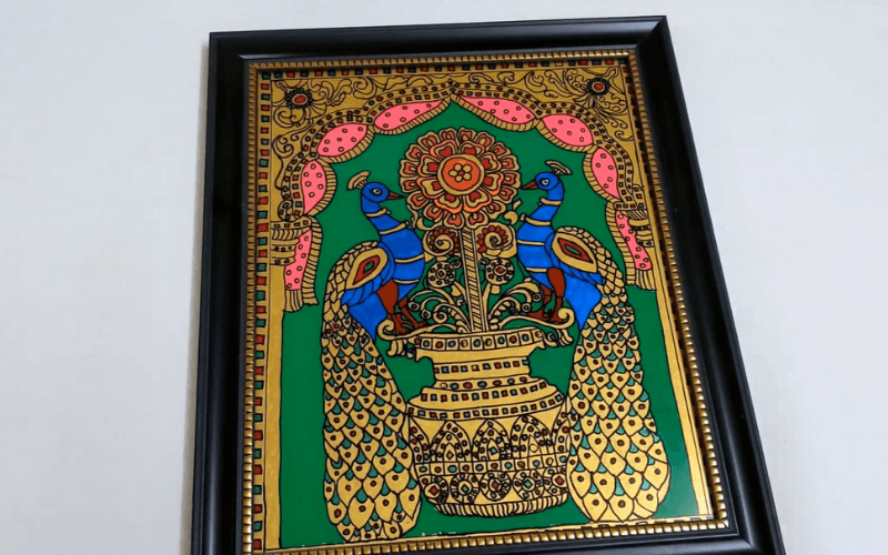 A framed Tanjore painting of peacocks - Image by Naveena Lifestyle