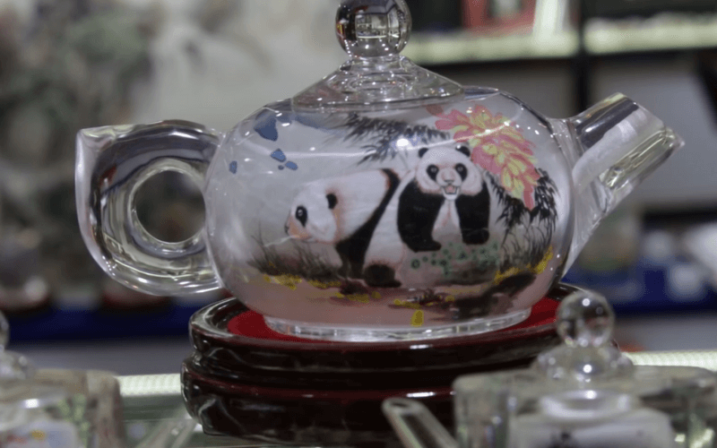 A glass teapot with reverse paintings of pandas - Image by Verasine