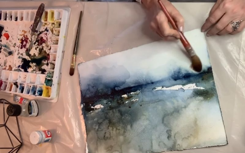 A painter shown adding finishing touches to an abstract watercolor painting