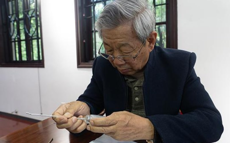 Wang Xiaocheng and holding a painted snuff glass - Image by China Daily