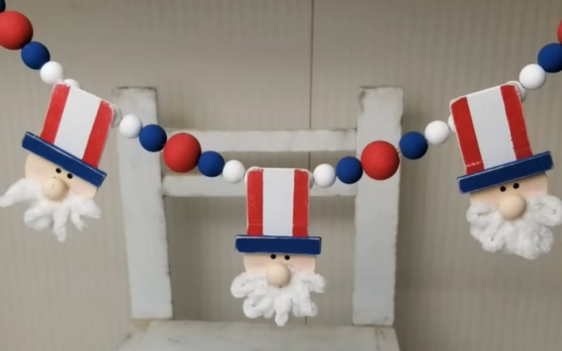 a bead garland punctuated with Uncle Sam heads made from discarded wooden toys