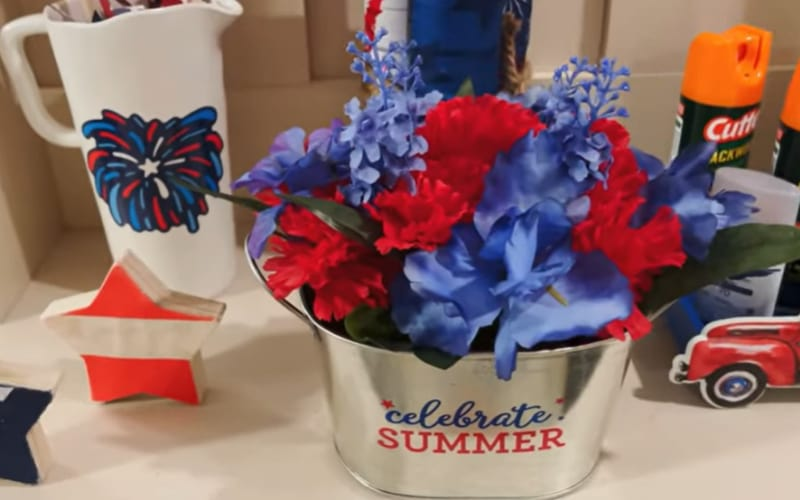 a beverage tub filled with blue and red flowers