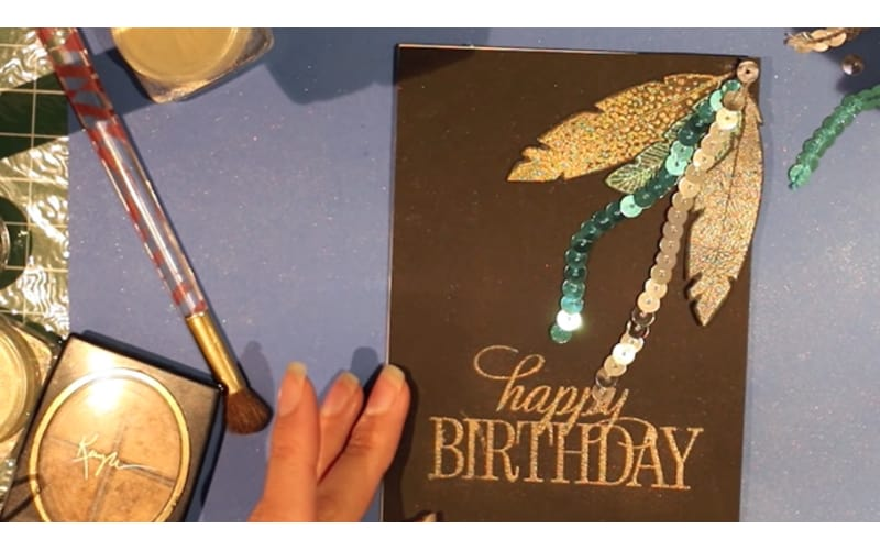 a birthday card made with DIY embossing powder with a makeup brush and eyeshadow makeup on the crafter's table