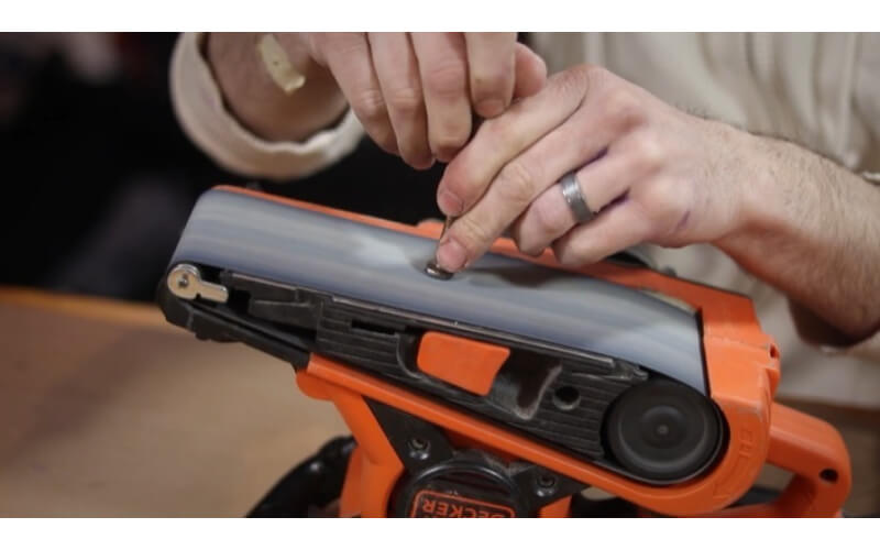 a crafter sanding off the markings on the head a stainless steel bolt using a portable sanding machine