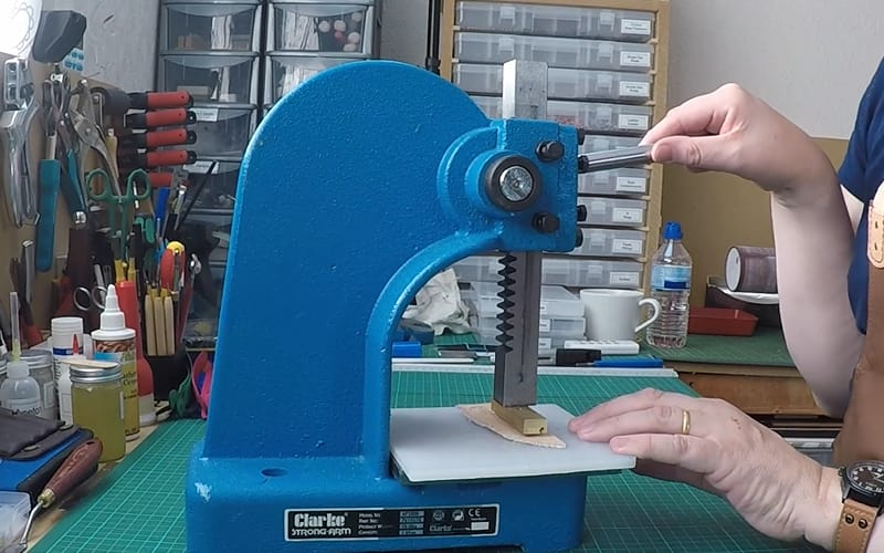 a crafter stamping a piece of leather using an arbor press