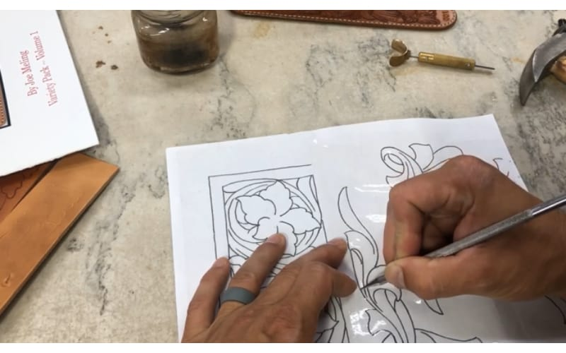a crafter transferring his design on leather by tracing