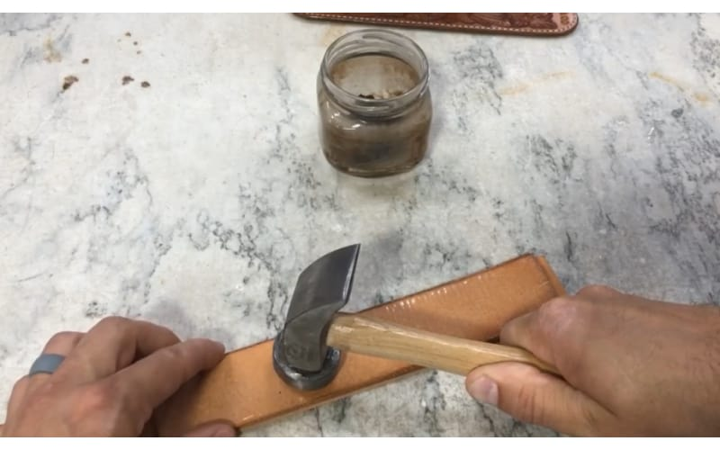 a crafter transferring the design to leather by tapping a leather pattern over it