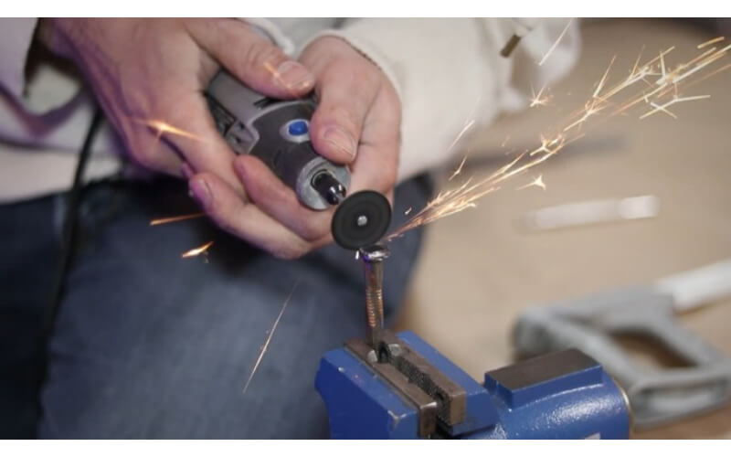 a crafter using a Dremel tool to cut off some parts of a stainless steel bolt mounted on a vise