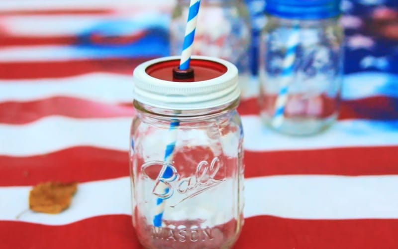 a DIY mason jar cup painted with red and white on the lid