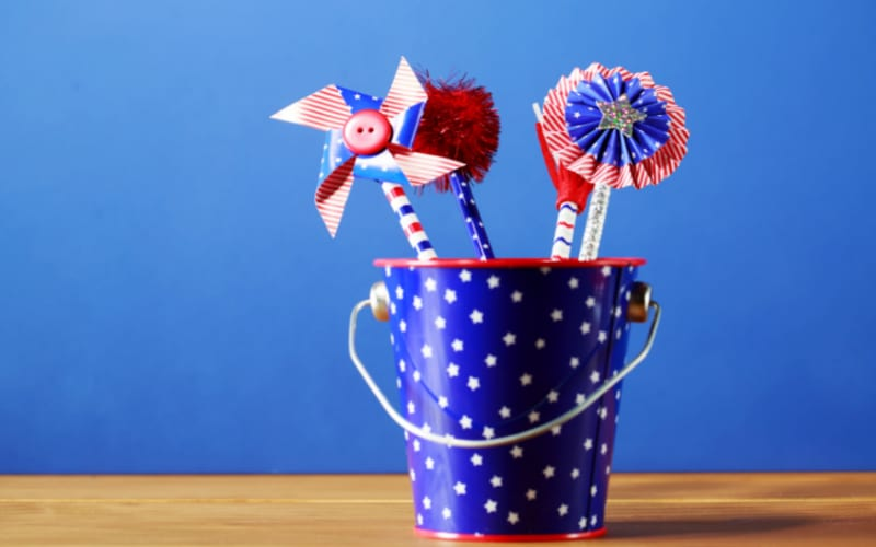 A festive bucket filled with pinwheels, a pompom, and other crafts that younger kids can make