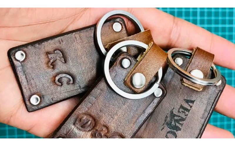 a hand holding three personalized leather keychains