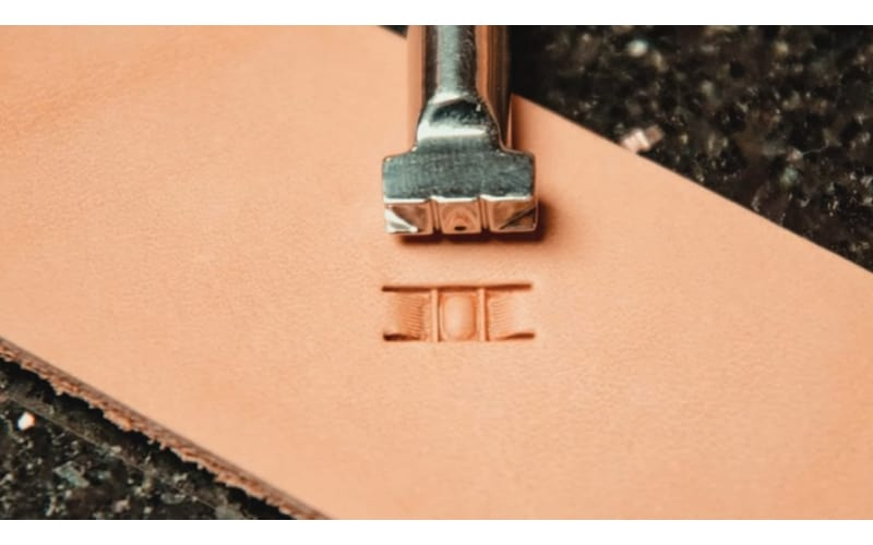 a metal stamp over a piece of leather