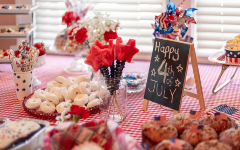 a party table decorated with 4th of July decors and laden with festive food