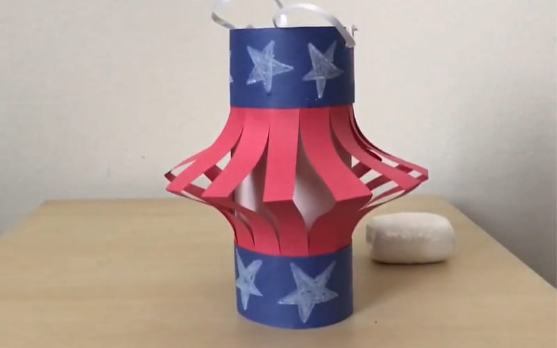 a patriotic lantern made from construction paper designed with stars