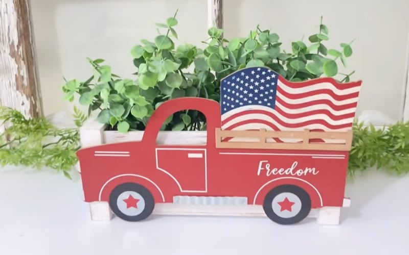a planter box decorated with a red vintage truck