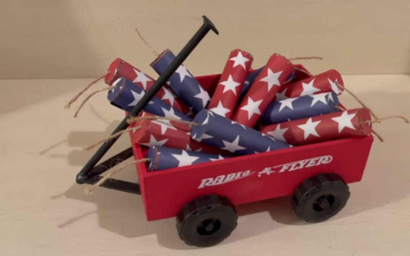 a red wagon filled with red and blue firecrackers