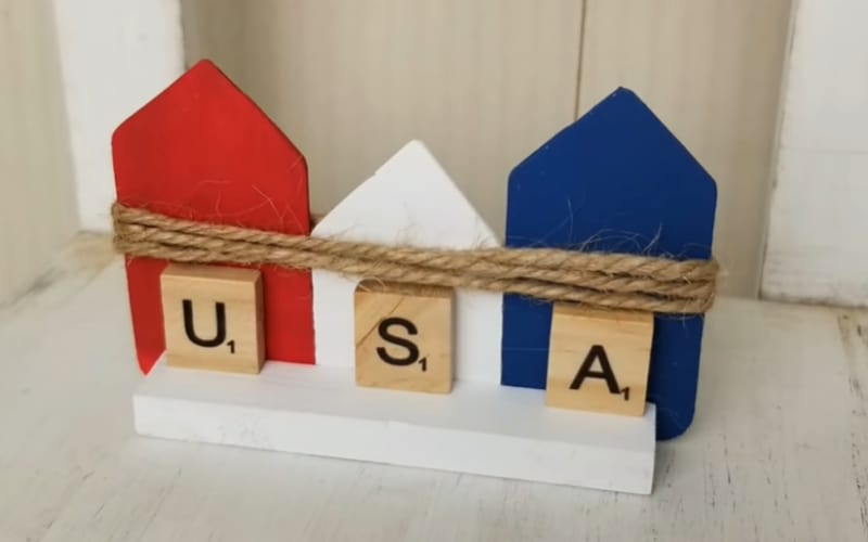 a row of a wooden outline of houses with the Scrabble letters U, S, and A glued to it