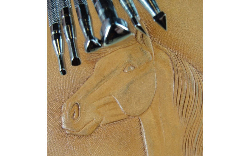 a set of figure carving tools on a piece of leather embossed with a horse head