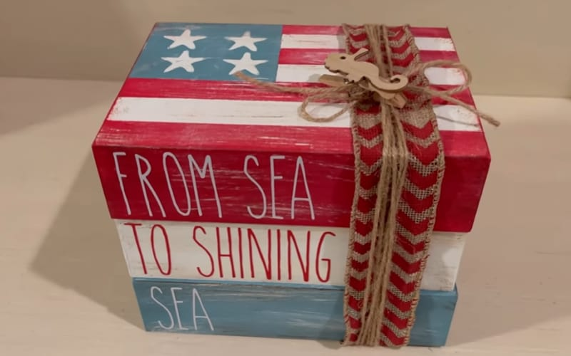 a stack of books made from wooden trays and painted with patriotic colors