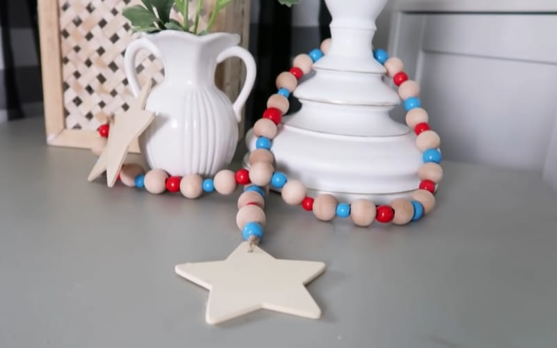 a string of patriotic beads with star ends around a white decorative vase