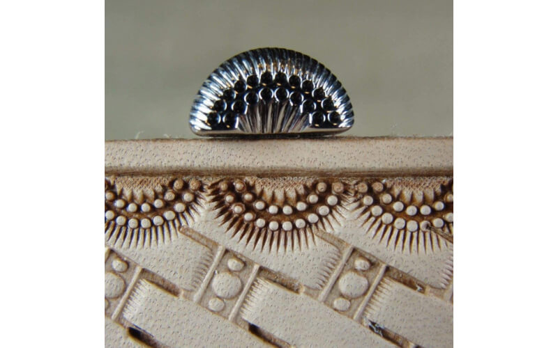 a sunburst border stamp and the embossed leather showing the results