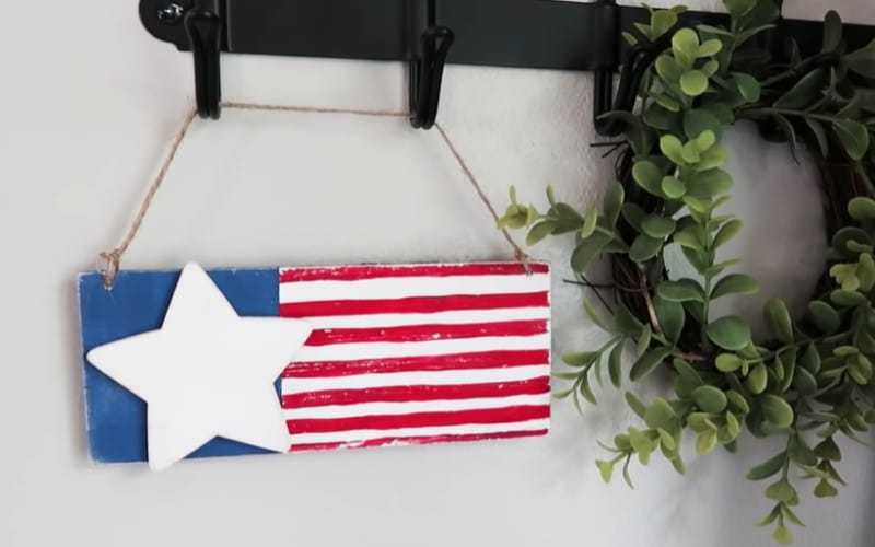 a wooden plaque painted with patriotic colors and a single wooden star