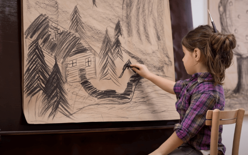 a young girl making a charcoal drawing