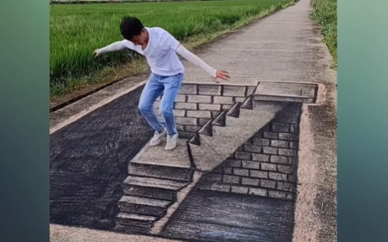 An artist frolicking on his 3D charcoal drawing on a cement road - Image by A LY TV