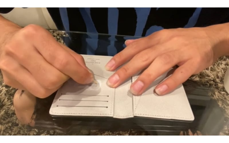 an image of a crafter lightly scratching a hot stamp with a toothpick