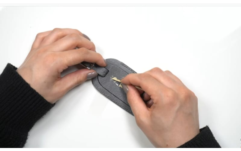 an image of a crafter removing hot stamping from a luggage tag using adhesive tape