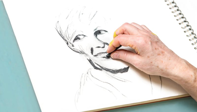 A woman drawing a face with charcoal vine