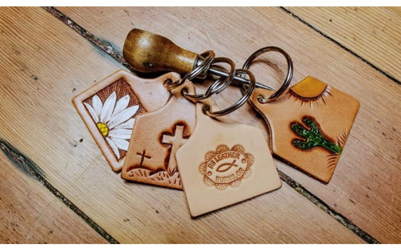 cow tag leather keychains with an awl on a table