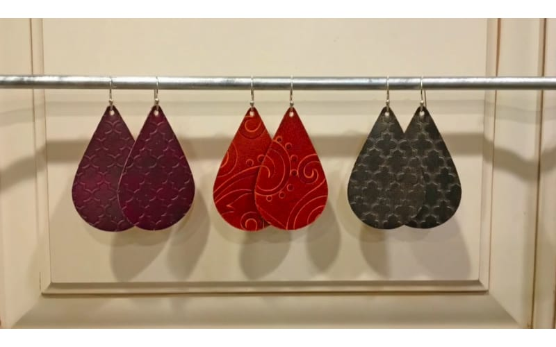 three pairs of embossed leather earrings hanging on a steel rod