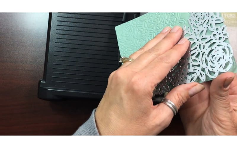 a crafter's hands removing the thin die from a card piece
