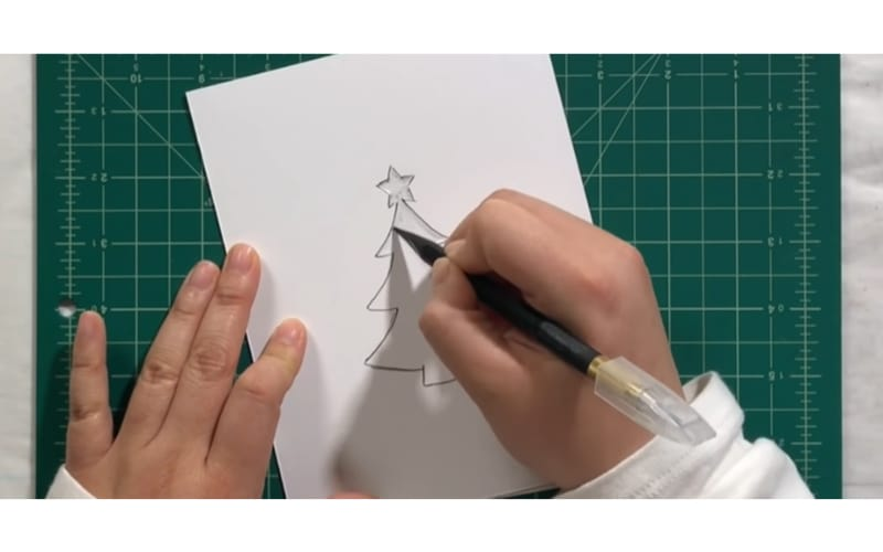 a crafter embossing a Christmas tree on thick white paper using a stencil as a guide