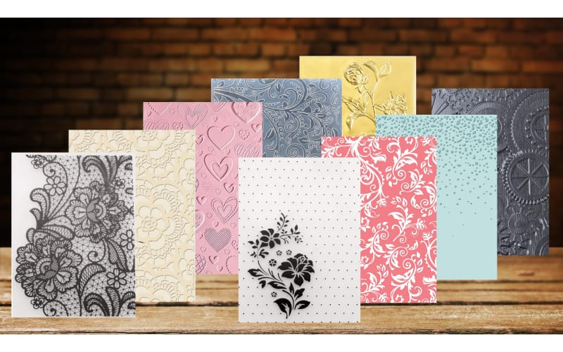 Various embossing folders standing on a wooden table