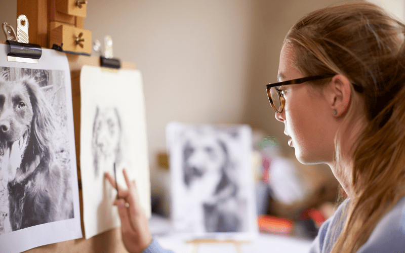 Side View of Female Teenage Artist Sitting at Easel Drawing
