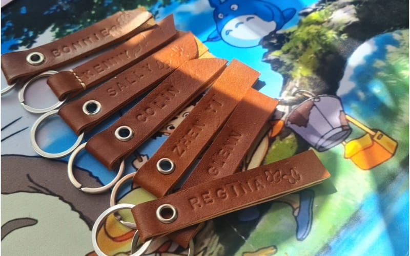 some personalized leather keychains on a printed mat