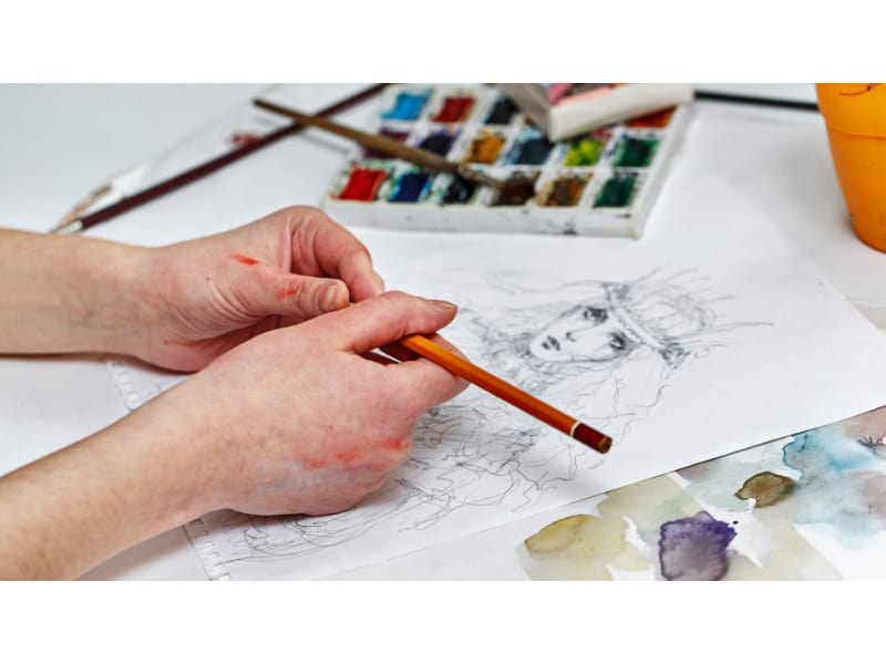 An artist using a pencil to draw a portrait using the scribbling shading technique.