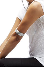 Person wearing 3 article22 arrow bangles above their elbow.