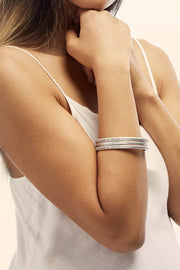 Woman wearing 3 peace bangle bracelets. Available at Sophie Stargazer.