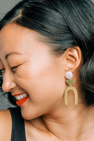 Woman wearing Pneuma arch earrings. Brass and white.