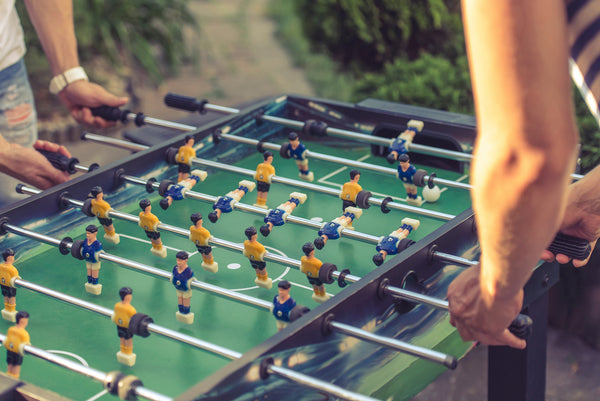 People playing and competing on a popular indoor foosball table.