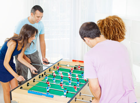 Family playing at a Garlando G-5000 foosball table at home.