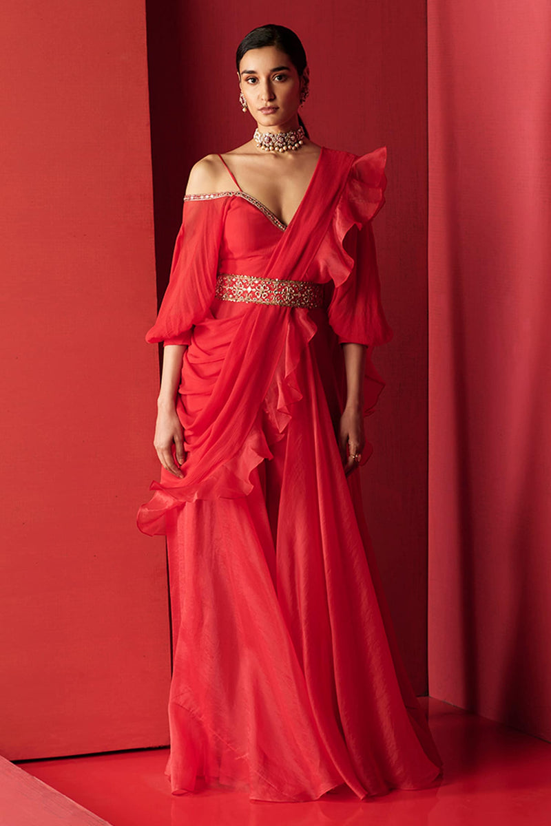 Red jumpsuit with embroidered neckline & off shoulder balloon sleeves. Paired with ruffle dupatta & embroidered belt.