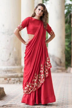 A red lehenga featuring an attached drape decorated with leaf embroidery in gold. It is teamed with a matching blouse and the set is crafted in cotton satin fabric.
