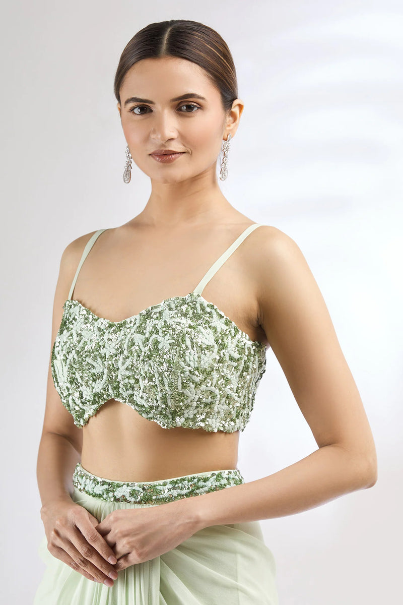 Green saree with sequin embroidered floral motifs on waistline. Comes with blouse and cape