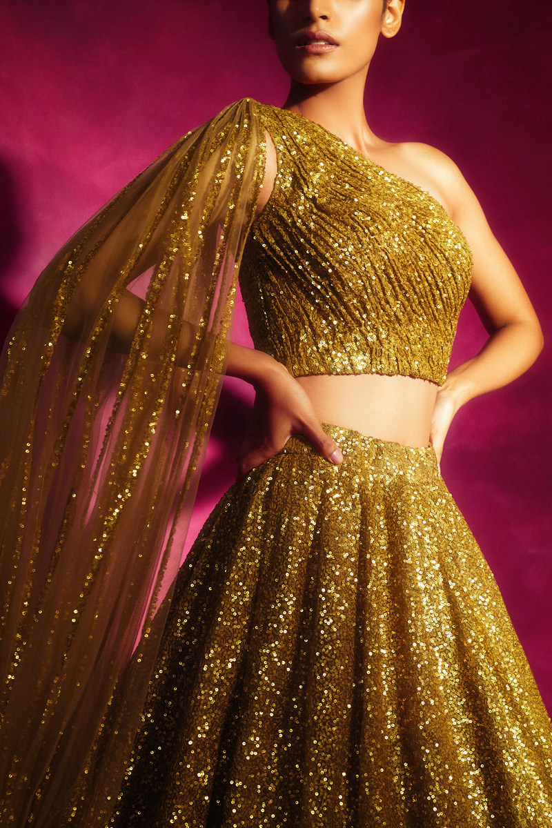 Dull gold lehenga with sequin embroidered detail. Paired with one shoulder sequin embroidered & attached veil blouse.