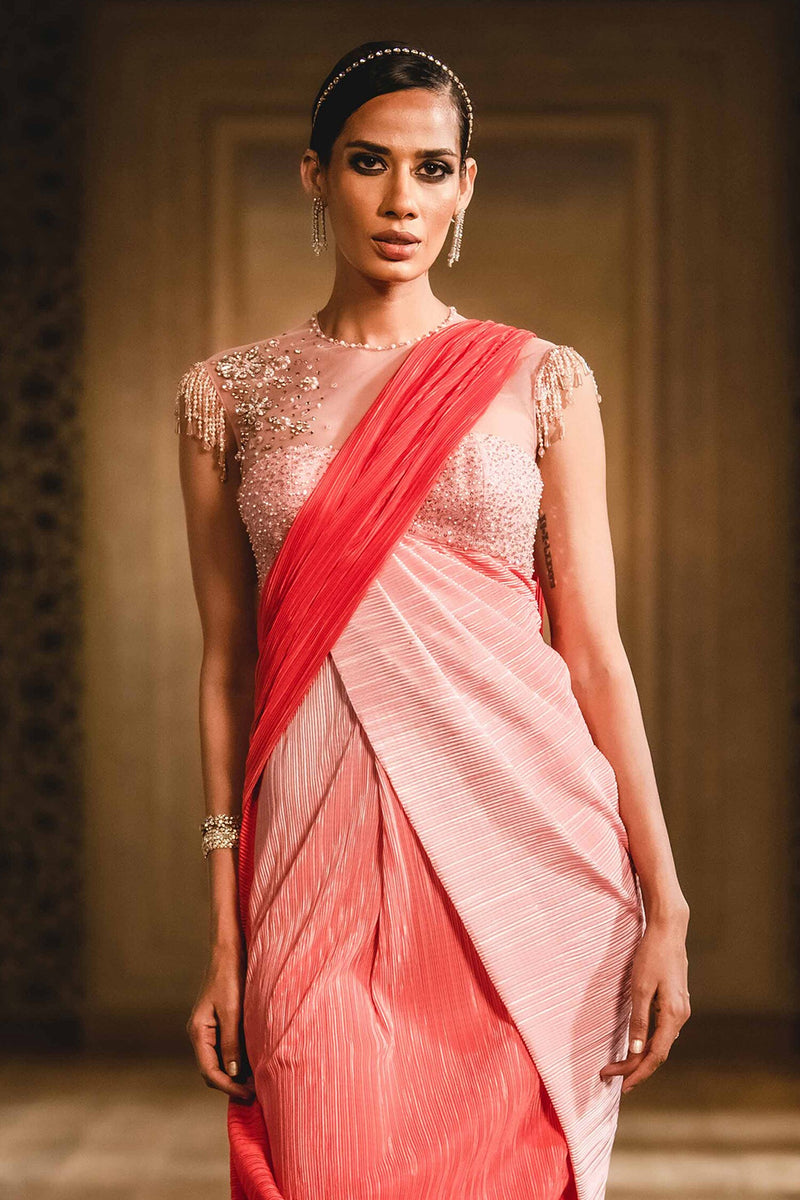 Coral ombre pre-draped saree with crinkled texture. Comes with resham & stone embellished blouse enhanced with bead tassels.