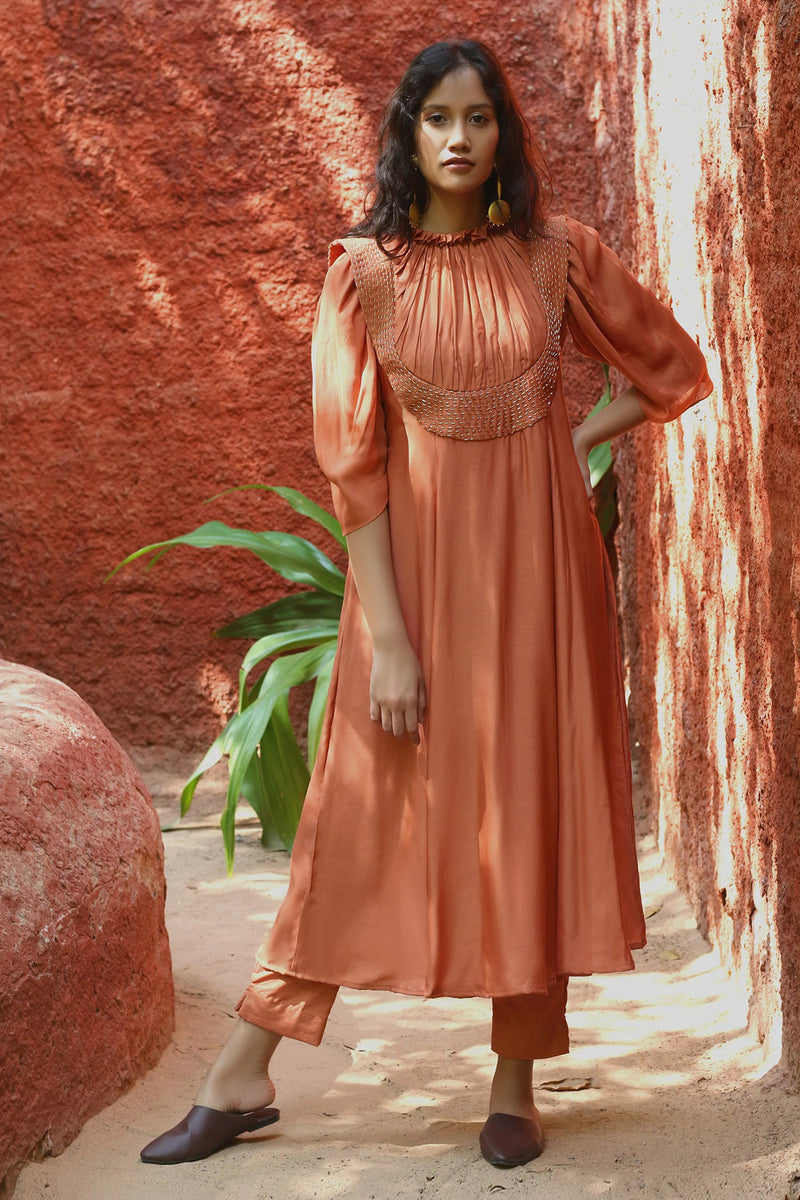 Rust anarkali with metallic bead work & pleated bodice. Paired with pant.